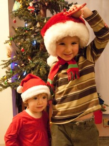 Two kids in Santa hats standing in fron of a Christmas tree